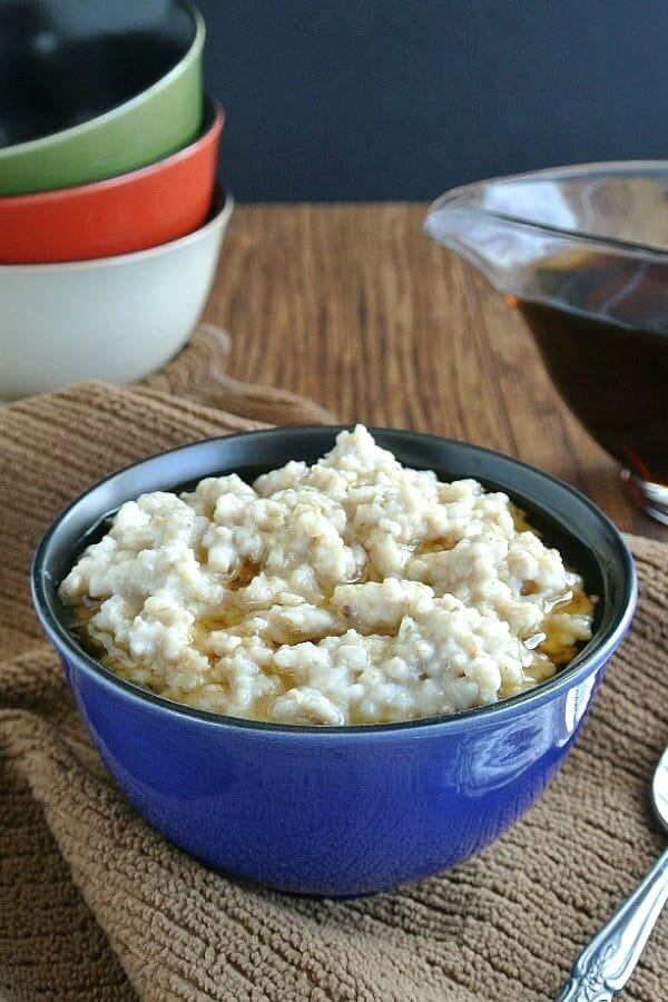 Slow Cooker Irish Oatmeal is filling a blue porcelain bowl with maple syrup floating on top.