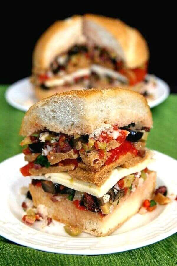 Four inch high sandwich with layers of boule, three kinds of olives, seitan and vegan cheese.