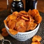 Air Fryer Sweet Potato Chips are overflowing a geometric black and white bowl tilted forward and spilling onto the brown beaded mat.