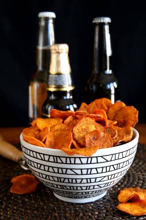 Air Fryer Sweet Potato Chips are overflowing a geometric black bowl with beers behind and an antique beer bottle opener on the side.
