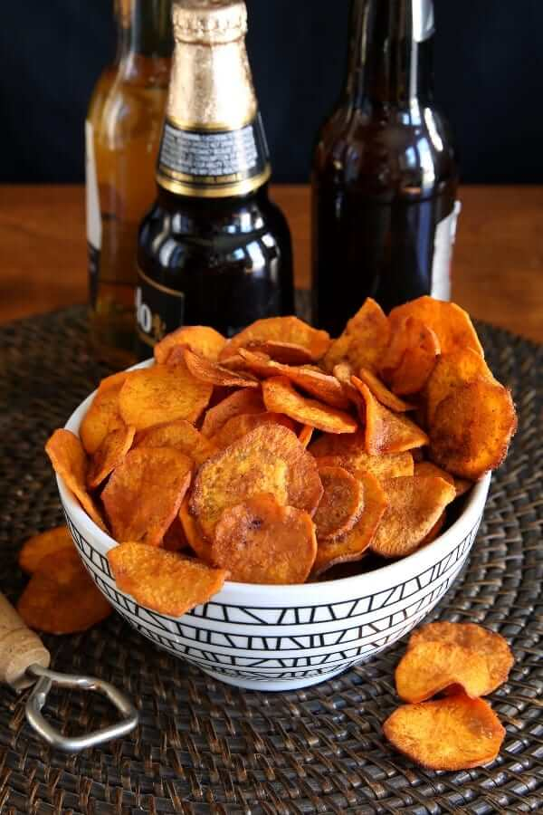 Air Fryer Sweet Potato Chips are overflowing a geometric black bowl with three different beer bottles standing behind.