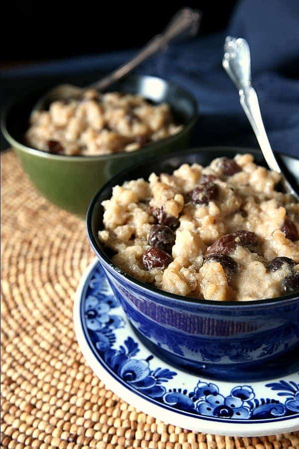 Up close cropped photo of creamy rice pudding filled with raisins with a spoon in it.