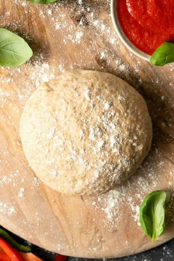 Overhead view of a perfectly round ball of pizza dough on a cutting board with flour.
