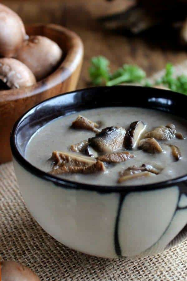 An Asian designed bowl is cropped for the photo and full of creamy mushrooms soup with extra wild mushrooms on top.