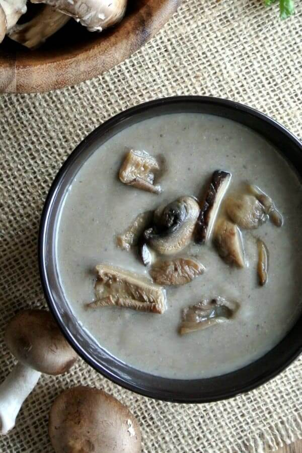 An overhead photo of a bowl full of creamy mushroom soup with wild mushrooms garnished in the center.