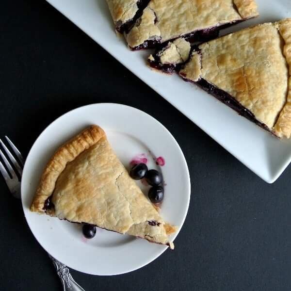 Overhead view of a baked pie with blueberries and sliced on a white plate.