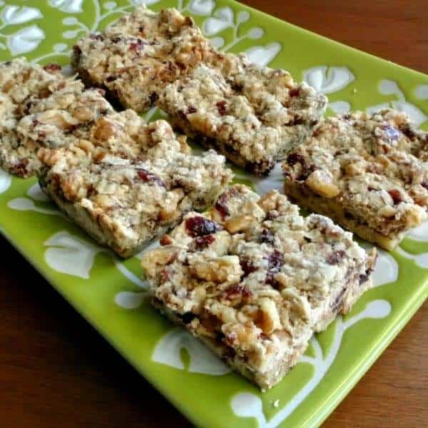 Angled front view photo and close-up up healthy snack bars cut into squares and showing cranberries and dates.
