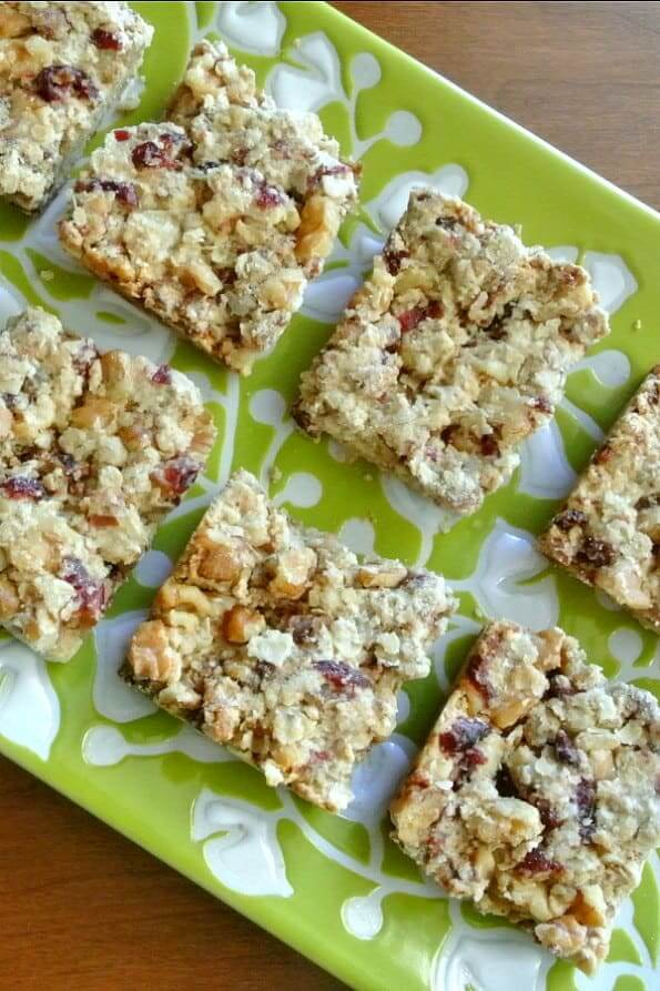 Close overhead photo of healthy snack bars cut into squares and showing cranberries and walnuts