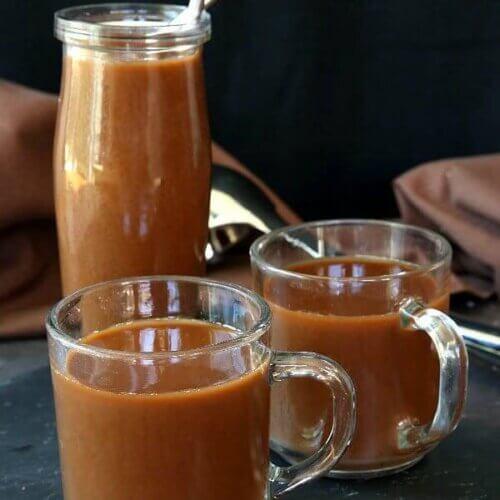 Two mugs full of mocha coffee with an iced coffee mocha behind.