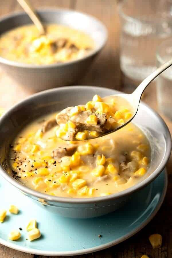 Close-up photo of a spoonful of corn chowder with chunks of meatless sausage and fresh corn kernels.