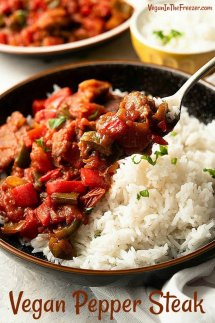 Close-up of a fork full of pepper steak mixture served over rice.