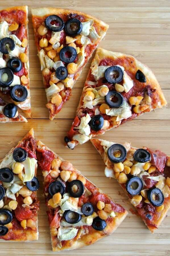 Overhead view of slices of pizza scattered with Mediterranean vegetables.