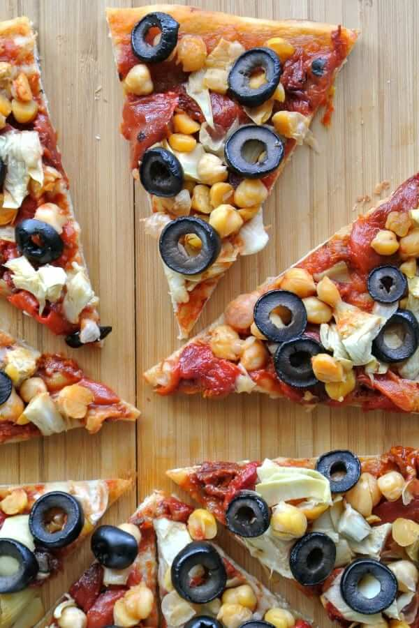 Overhead view of a close-up of a circle of sliced pizza on a wooden cutting board.