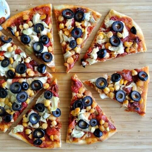 Overhead photo of pizza with all the pieces spread apart in a circle on a wooden cutting board.
