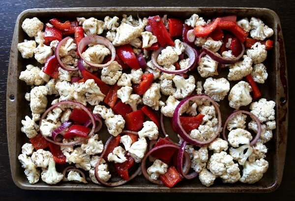 Marinated cauliflower, bells and onions are spread out evenly on a baking sheet.