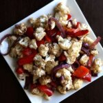 Overhead view of roasted cauliflower and veggies caramelized on a square white plate.