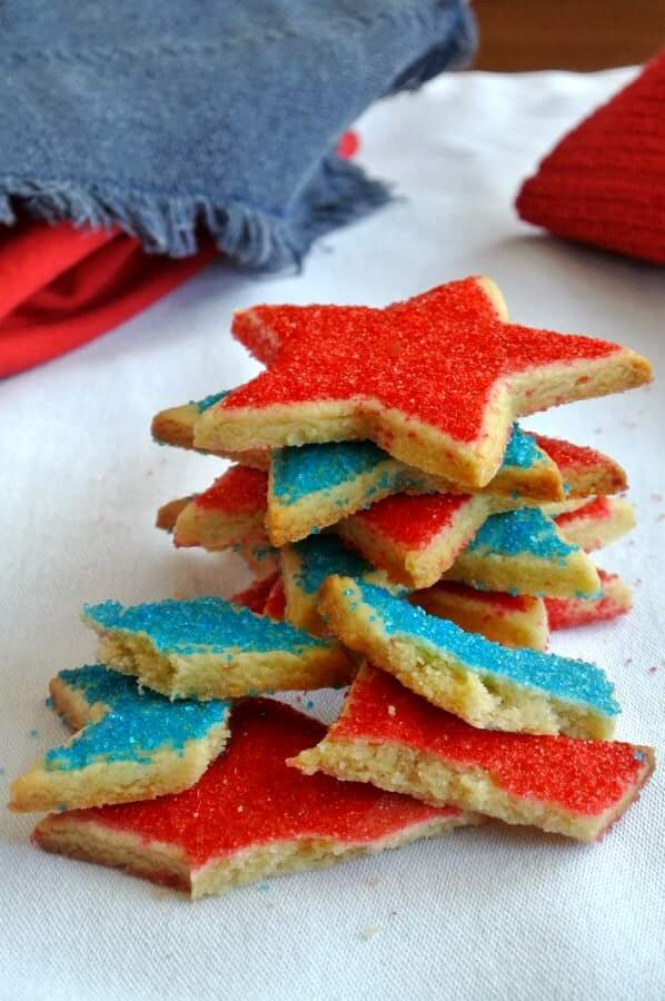 Stars Shortbread Cookies in the colors of red and blue and are stacked high with cookies broken in front.