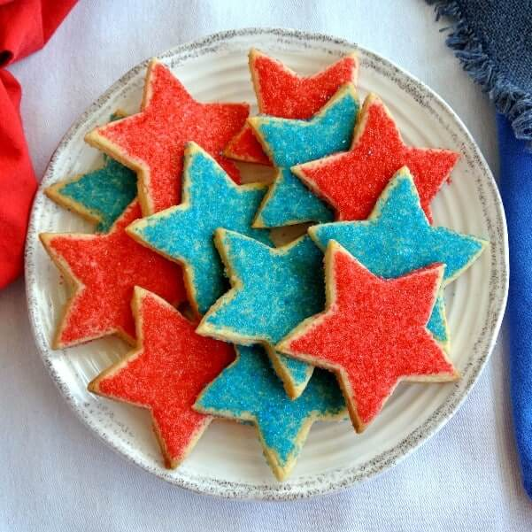Star shaped Shortbread Cookies in the colors of red and blue and are piled on a plate and are photographed from above.