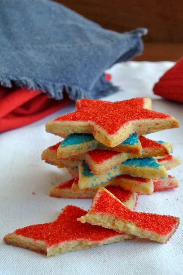 Stack of six stars shortbread cookies sitting at all angles and covered with red and blue sugar for the 4th of July.