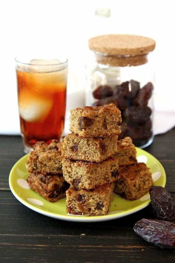 Stack and pile of banana bread squares infront of a glass of iced tea and a jar of dates.