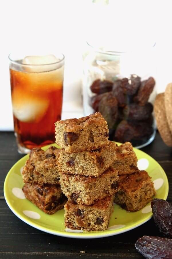 Stack and pile of banana bread squares infont of a glass of iced tea and a jar of dates with lid off.