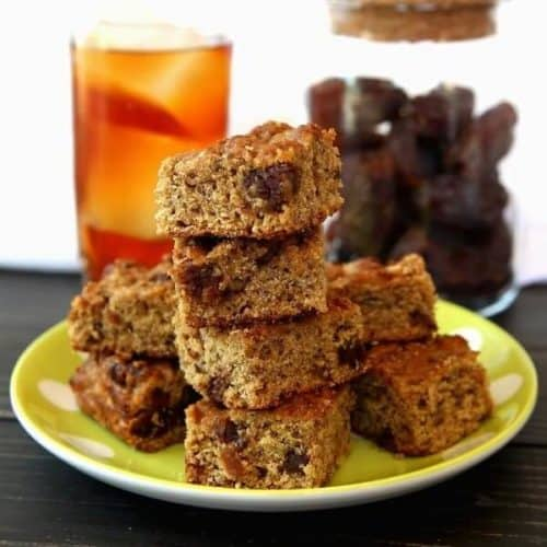 Stack and pile of banana bread squares infont of a glass of iced tea and a jar of dates.
