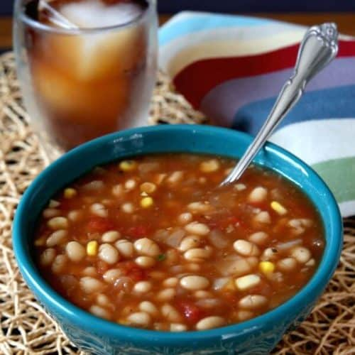 Navy Bean Soup in a turquoise bowl with a spoon laying inside and iced tea over ice behind.
