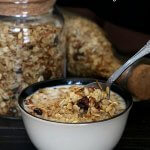 A bowl full of granola is being scooped up for a bite. With two jars of homemade cereal behind.