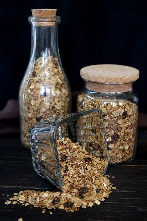 Three glass containers full of homemade granola cereal with the front container overflowing.