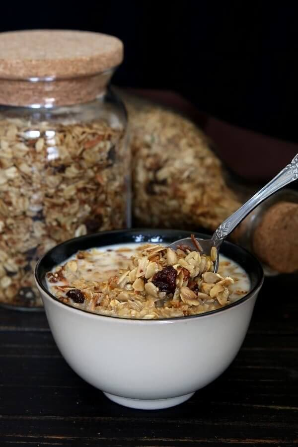A bowl full of nut free granola is being scooped up for a bite. With two jars of homemade cereal behind.