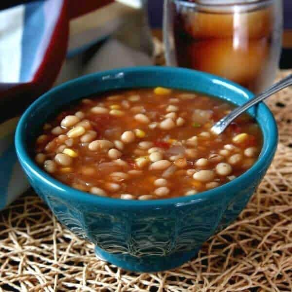 Navy Bean Soup in a turquoise bowl sitting on an ivory woven mat with a spoon inside the soup.