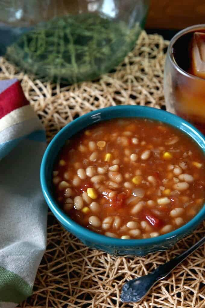 Navy Bean Soup in a turquoise bowl sitting on an ivory woven mat with a spoon on the side.