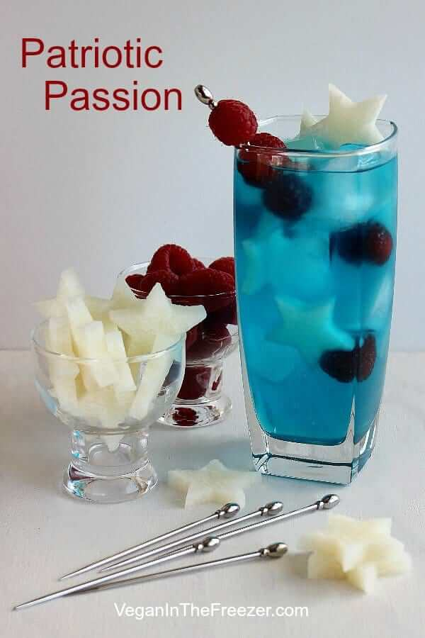 A tall glass of a blue cocktail with red raspberries and jicama stars.
