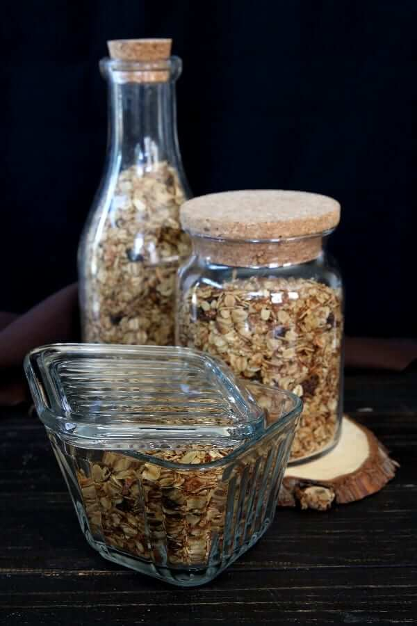 Three glass containers full of homemade granola cereal sitting on a dark wooden table.