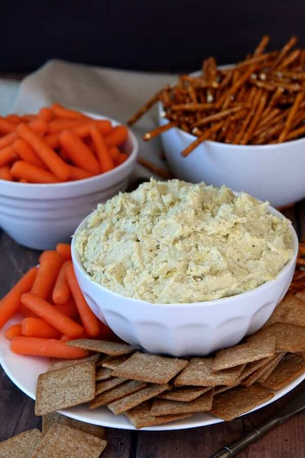 White bowl filled with artichoke hearts dip with wheat thins and baby carrots piled around the bowl.