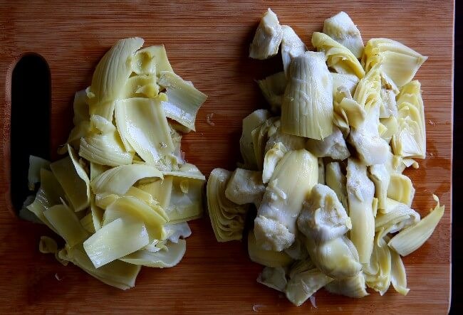 Overhead photo os quartered artichoke hearts on one side and discarded tough leaves on the other.