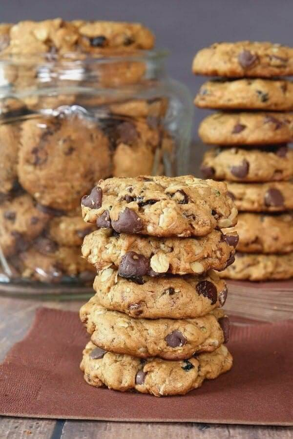 Five cookies are stacked high on a brown napkin with more cookies stacked behind.
