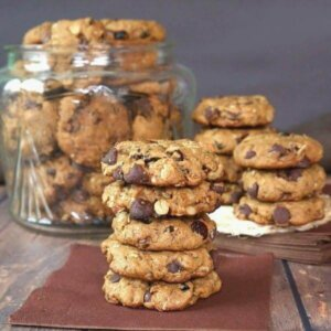 Five cookies are stacked high on a brown napkin with chocolate chips pied in a cookie jar behind.