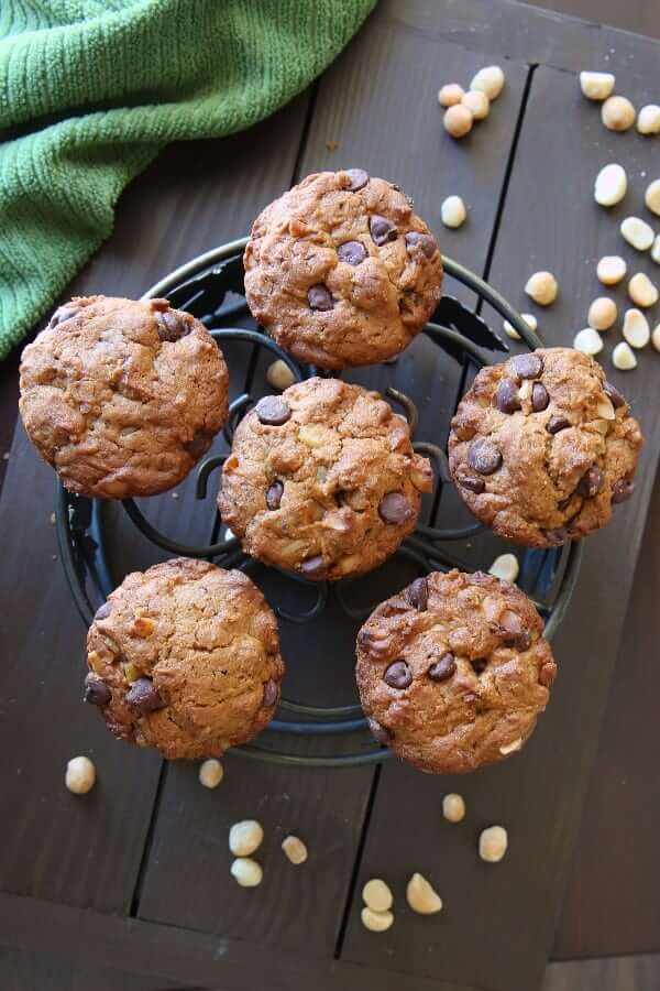 Overhead view of six perfectly placed vegan muffins chocolate and nuts filled, on an iron trivet with macadamia nuts scattered around.