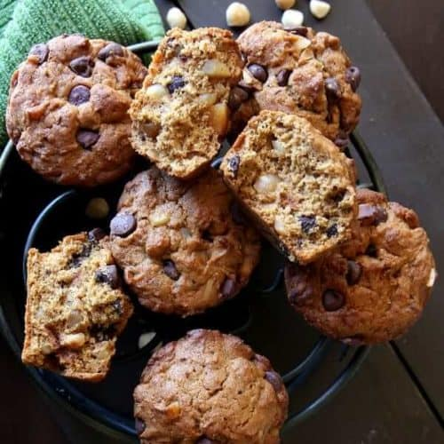 Overhead view of chocolate chip and macadamia nut filled muffins on an iron trivet turned every which way.