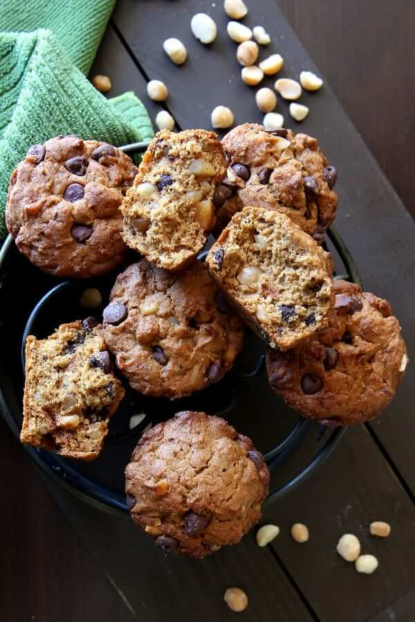 Overhead view of vegan muffins chocolate chip and macadamia nut filled muffins on an iron trivet turned every which way.