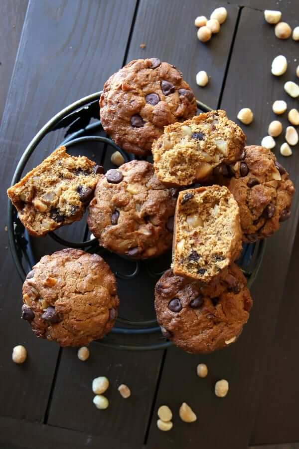 Overhead view of vegan muffins chocolate chip and macadamia nut filled, with some broke in half on top of an iron trivet.