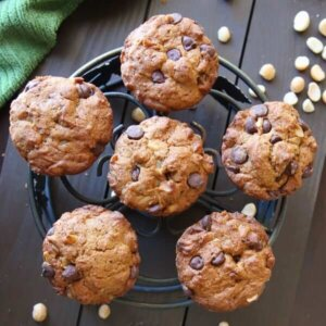 Overhead view of six perfectly placed muffins on an iron trivet with a green cloth napkin in the corner.