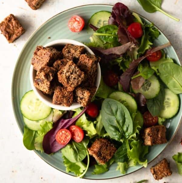 Overhead photo of a bright green salad with croutons in a small bowl sitting on the same plate.