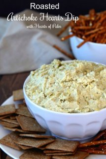 Cropped white bowl tilted forward and filled with artichoke hearts dip with wheat thins around the plate.