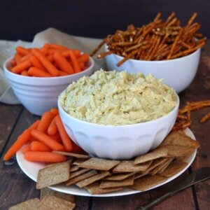 Square photo of a bowlful of creamy dip surrounded by pretzels, chips and carrots.