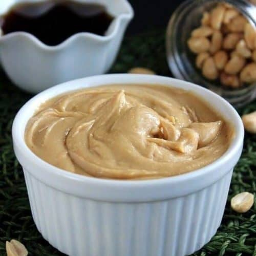 Straight view of peanut butter in a white bowl on an forest green mat with peanuts around.