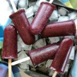 Overhead view and close-up of deep purple blueberry popsicles on a bed of ice.