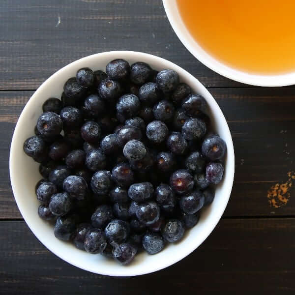 Overhead view of a closeup of fresh blueberries and orangy apple juice.