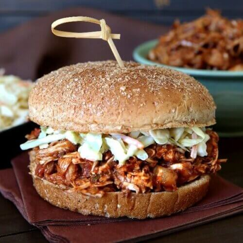 Front view of a fat sandwich on a bun with coleslaw and a bowl of more BBQ jackfruit behind.